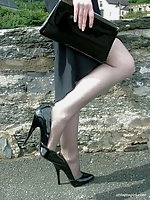 Cute redhead Miranda flashing her shiny stilettos and stockings by the lake